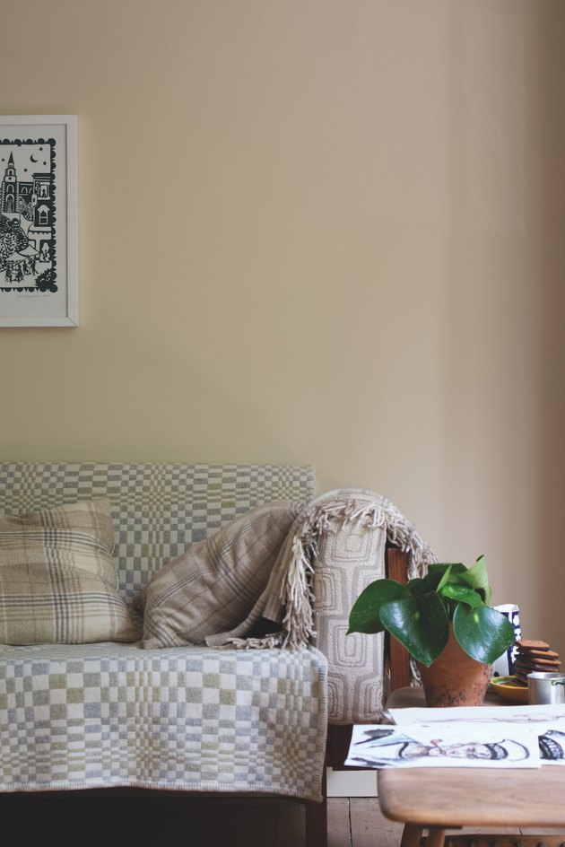 living room space with patterned textiles and neutral wall