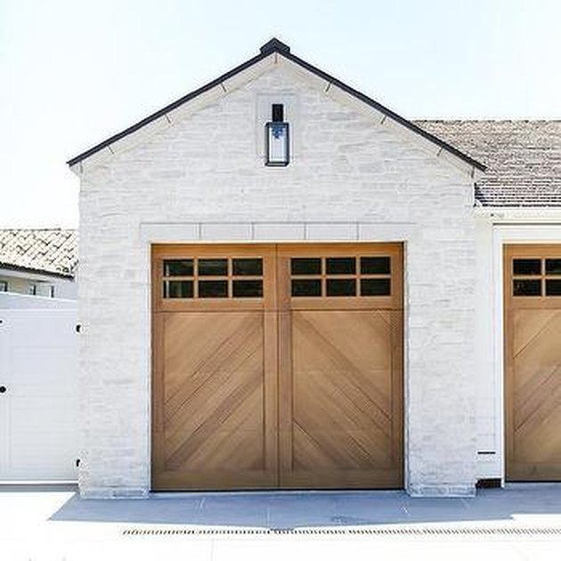 chevron patterned wooden garage doors on white home exterior