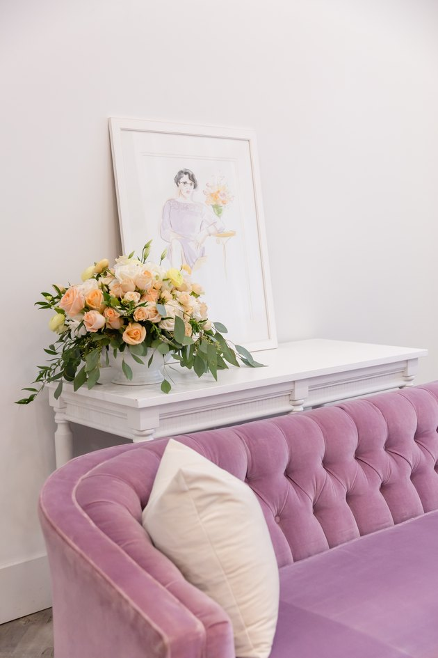 pink tufted sofa with white console table and framed artwork
