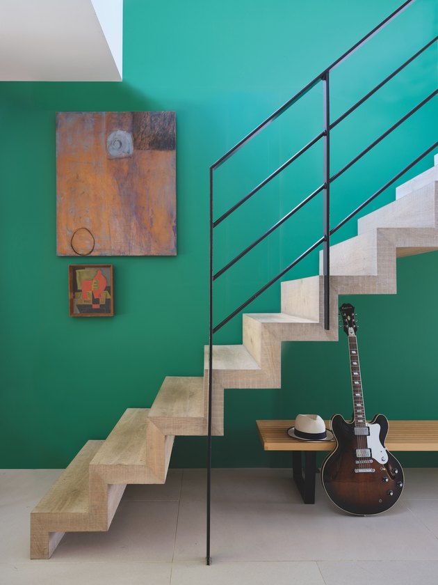 staircase with black rail and green wall