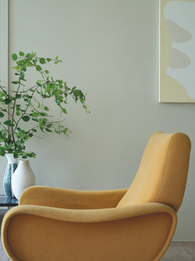 yellow chair with plant and neutral wall