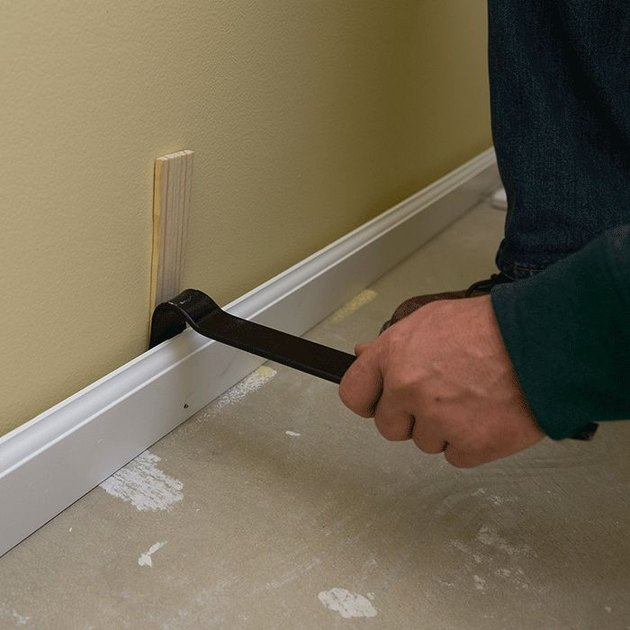 Prying off baseboards.