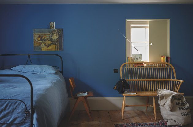 bedroom with blue wall and wood chair