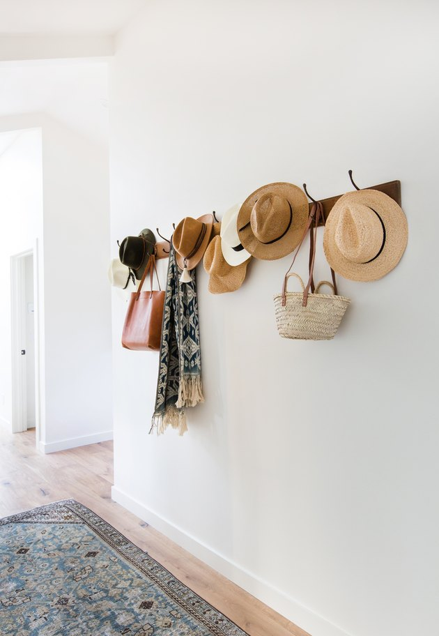 Hats and bags are organized on hooks in this hallway.