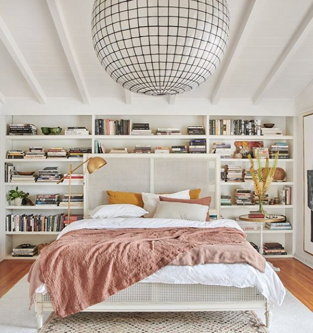 white bedroom with  floor-to-ceiling bookcase and statement chandelier