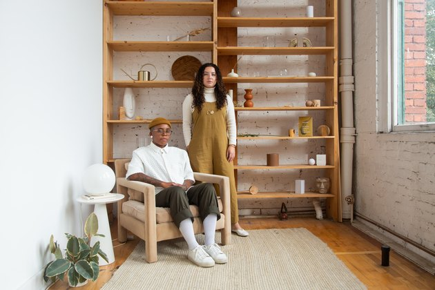 one person sitting and another standing near a shelf