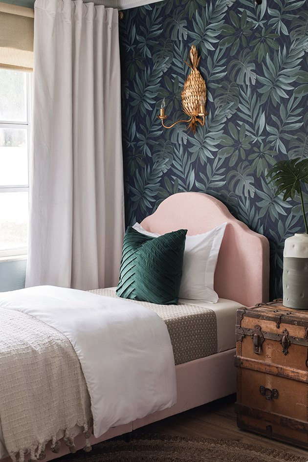 Patterned wallpaper bedroom color idea with upholstered pink headboard and brass wall sconce