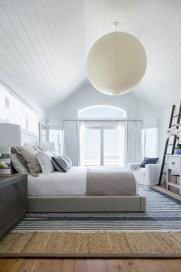 large round bedroom chandelier hanging from A-frame ceiling