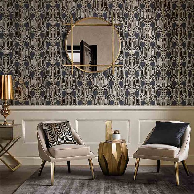living room space with art deco wallpaper, two chairs and mirror