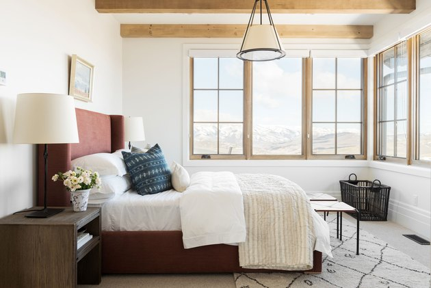 rustic bedroom chandelier hanging above bed with upholstered headboard