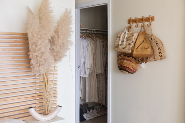 wooden headboard near open closet and wood hooks with bags