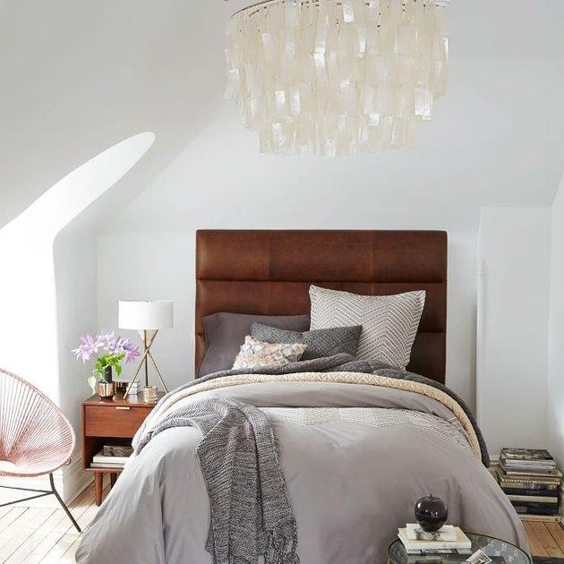 Lustre de chambre suspendu au-dessus du lit avec tête de lit rembourrée en cuir