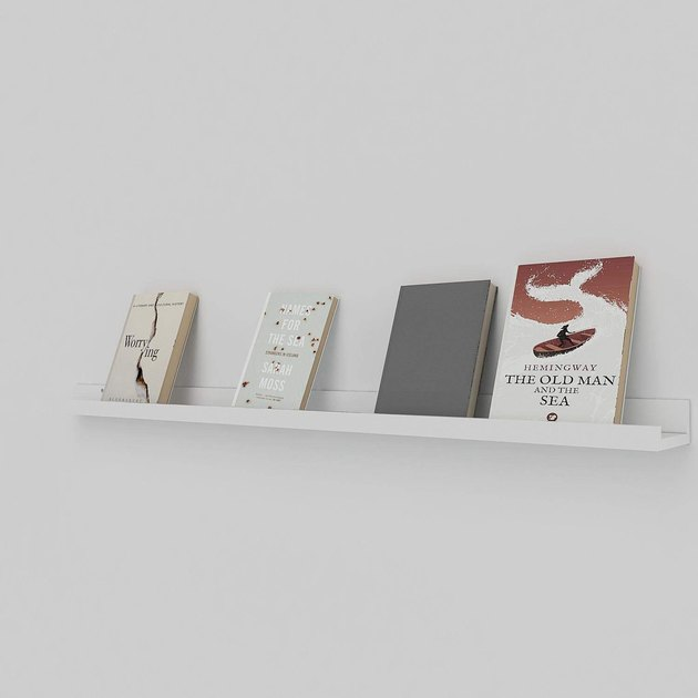 Long white ledge shelf displaying four books