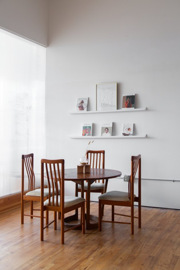 wood table and chairs with white shelves, magazines, and artwork nearby