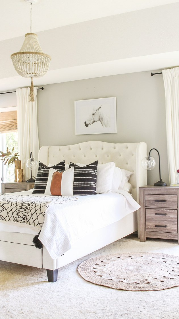 contemporary neutral bedroom color idea with chandelier and tufted headboard