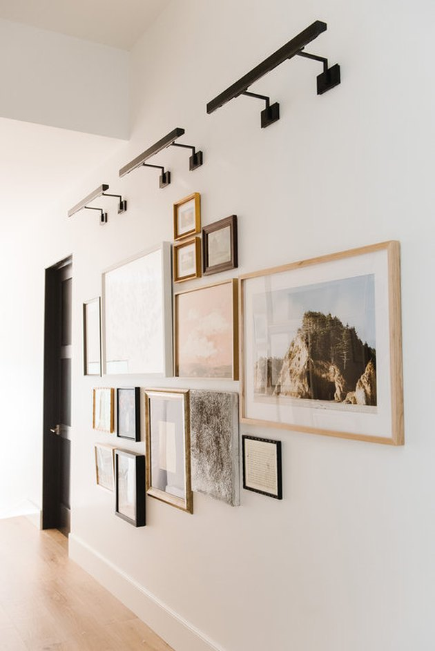 wall with artwork in various frames and lighting fixtures above