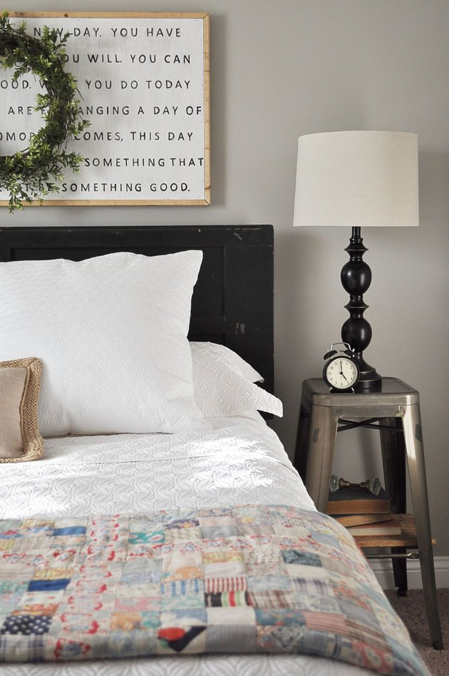 griege bedroom color idea with industrial side table and colorful quilt