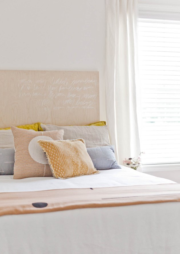 Pastel bedroom color idea with white walls and curtains at window