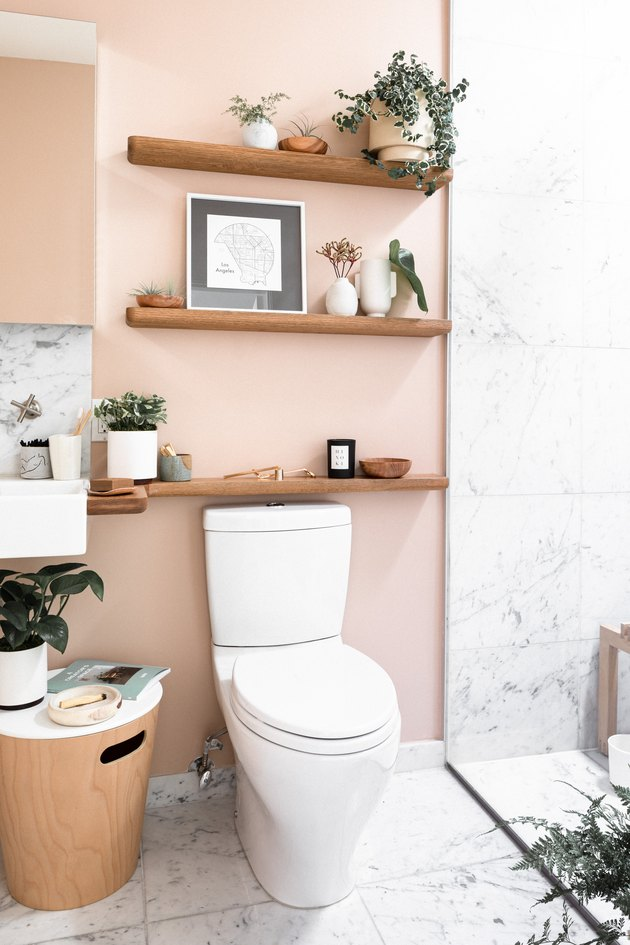 toilet with light pink wall, three wood shelves and decorations