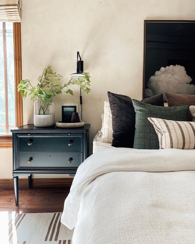 neutral bedroom with industrial wall sconce and painted black nightstand