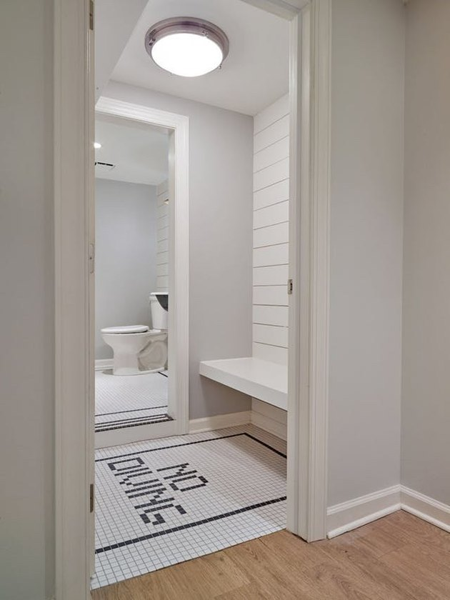bathroom with black and white mosaic floor tile and shiplap walls