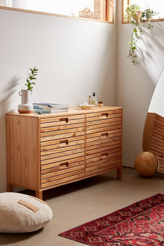 slatted dresser with plants and pillow nearby