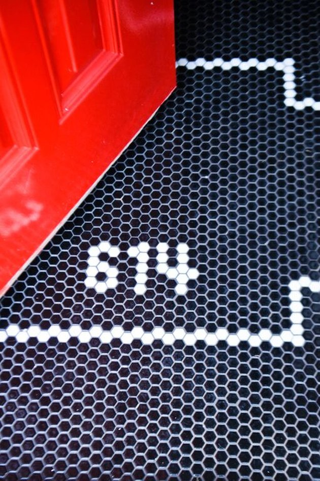 entryway with red door and black and white hex tile