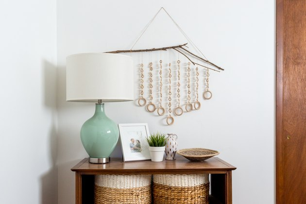 wood wall hanging with table and teal-colored lamp
