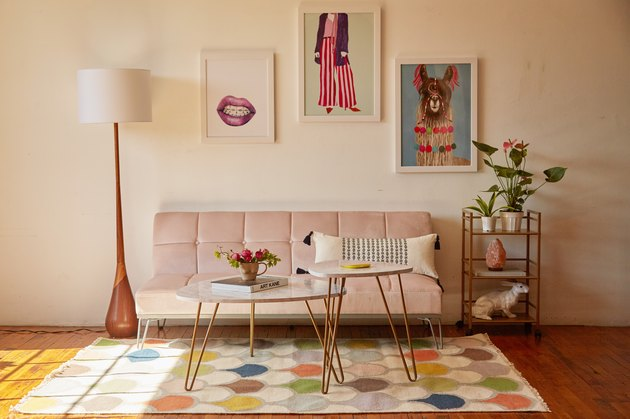 living room with pink futon and wall art