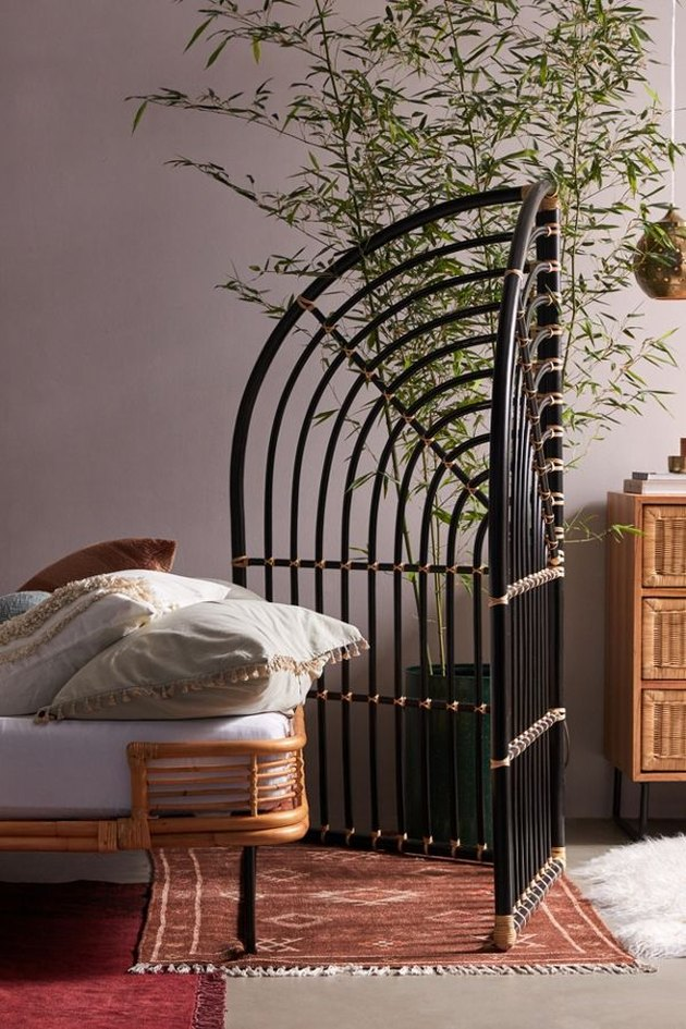 black rattan room divider near bed