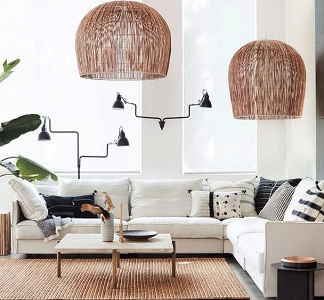bohemian living room lighting idea with rattan pendants and articulating wall sconces