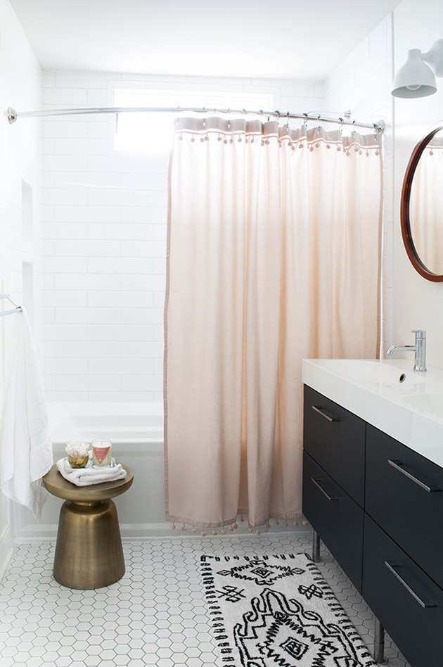 A bathroom with a pink shower curtain