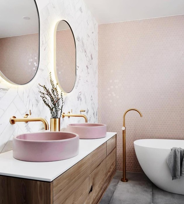 A bathroom with a pink tile wall