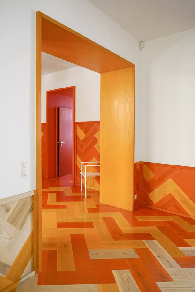 Orange door, floors, and walls in hallway