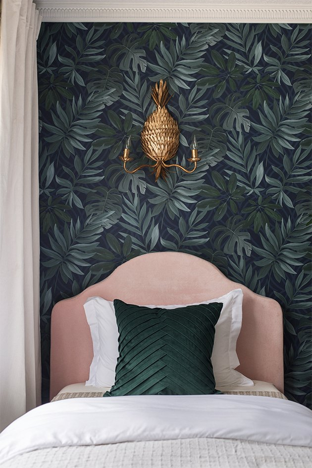 bohemian bedroom lighting idea with pineapple shaped wall sconce above pink upholstered headboard