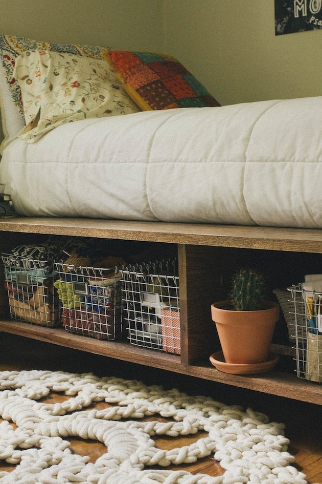 Wooden shelves with wire storage baskets and a cactus