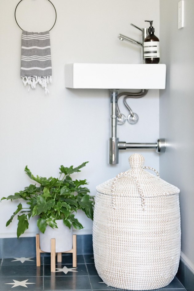 Small bathroom sink with basket hamper and plant