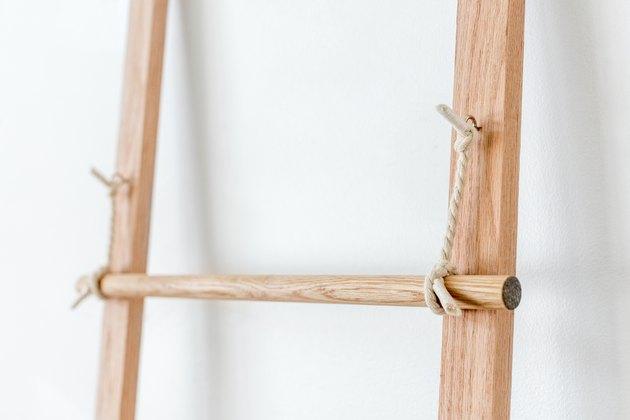 Fixez les barreaux de l'échelle aux morceaux de corde suspendus.