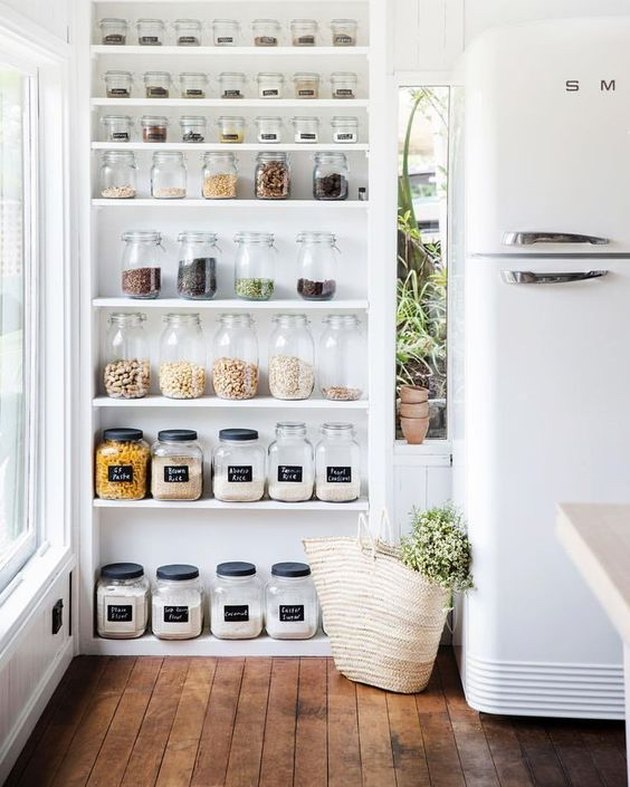 organized small pantry closet with glass jars and containers