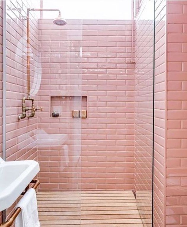 pink bathroom with exposed plumbing and wood floor