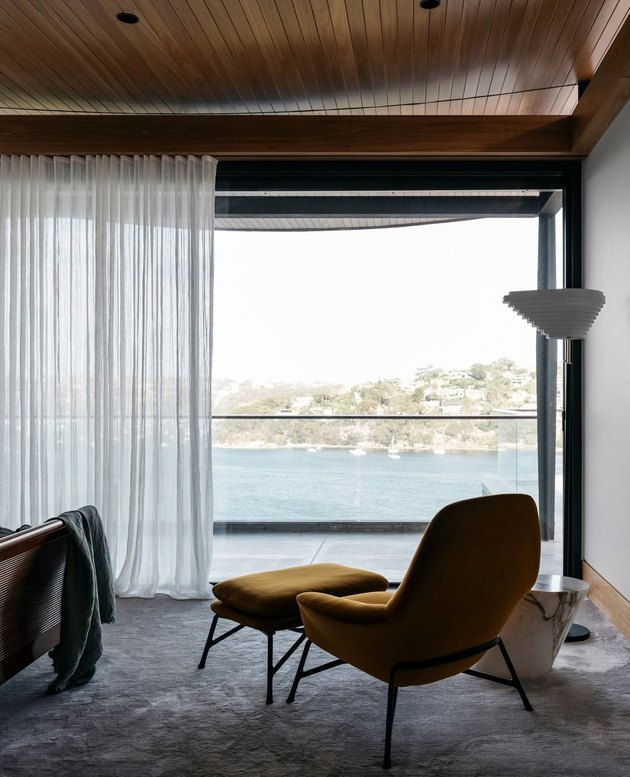 Contemporary apartment with mustard chair and current floor lamp