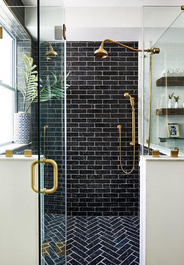 contemporary black tile shower and white grout and brass fixtures