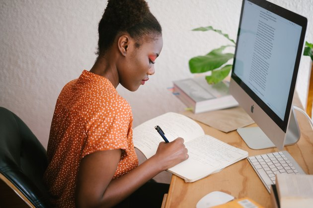 Black woman writing in notebook in front of apple desktop computer