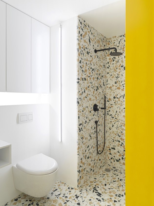 yellow and white contemporary shower with terrazzo