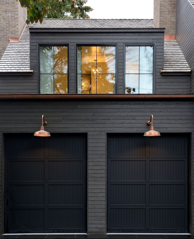 black exterior with black garage doors and copper wall sconces