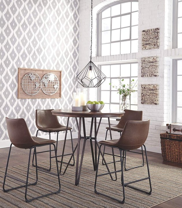dining space with four bar stools and gray wallpaper