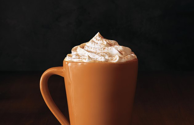 tall orange mug filled with pumpkin spice latte and whipped cream