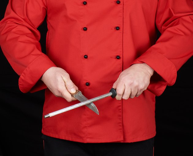 chef in red uniform sharpens a knife