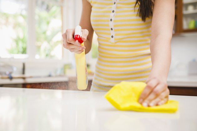 Hispanic woman spraying and wiping counter