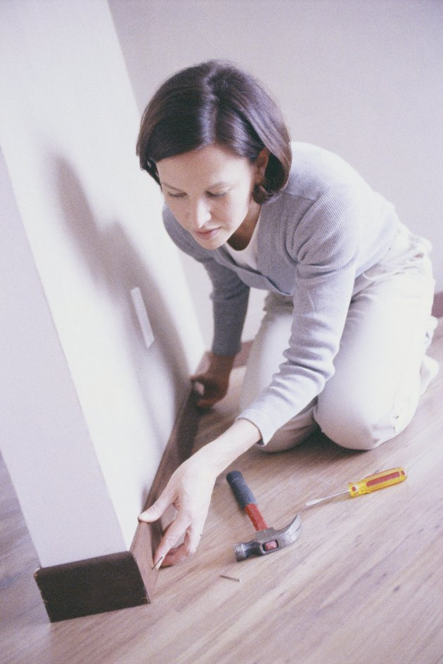 Woman Installing Baseboard